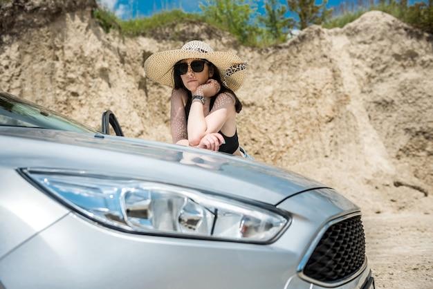 Piękna noga w pobliżu samochodu pozuje na piaszczystym brzegu podczas letnich wakacji