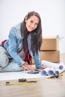 Piękna nowa właścicielka domu kobieta siedzi na podłodze w otoczeniu planów, używając kalkulatora.
