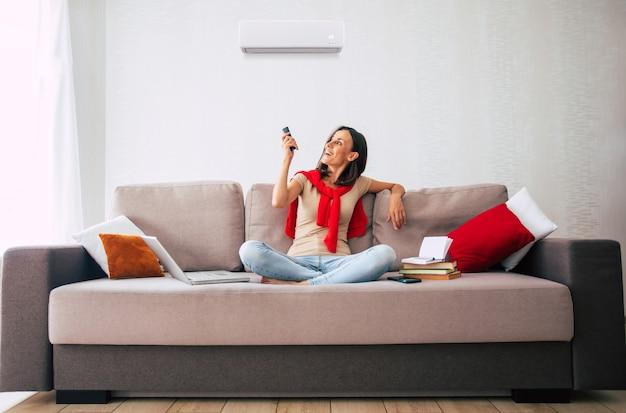 Piękna, nowoczesna brunetka używa klimatyzatora siedząc na kanapie i odpoczywając w upalny dzień