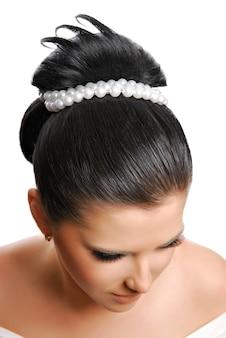 Piękna nowoczesna fryzura ślubna z perłami na białym tle