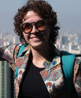 Piękna, nowoczesna kobieta pozuje do aparatu w okularach przeciwsłonecznych z sao paulo city w tle.