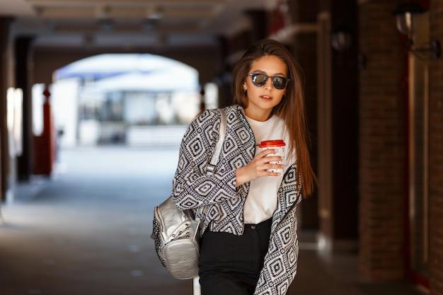 Piękna nowoczesna młoda dziewczyna pije kawę z okularami przeciwsłonecznymi w modnej kurtce spacery po mieście