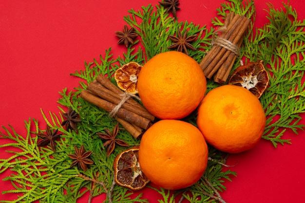 Piękna noworoczna kompozycja z mandarynkami na czerwonym tle. nowy rok i boże narodzenie