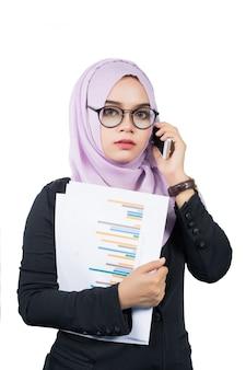 Piękna nowożytna młoda azjatycka muzułmańska biznesowa kobieta trzyma cellphe i raporty odizolowywający,.