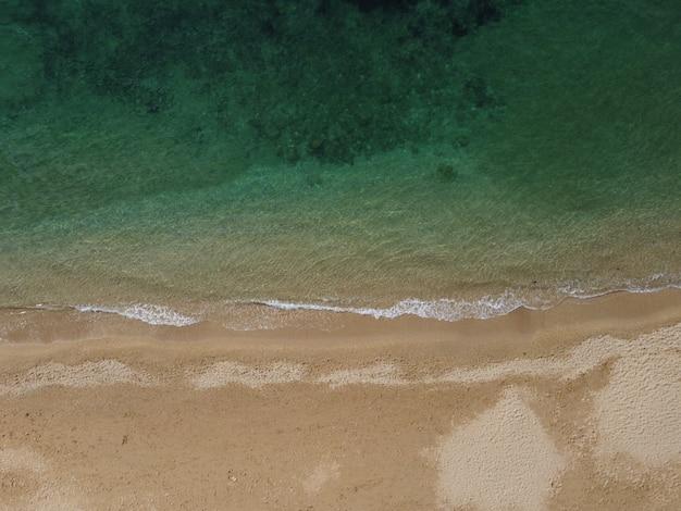Piękna odległa plaża z krystalicznie czystą, lazurową wodą z lotu ptaka, nietknięta przyroda i ukryta piaszczysta?