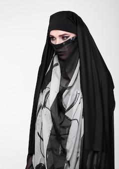 Piękna oko kobieta jest ubranym mody burkę na szarość