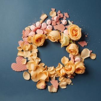 Piękna okrągła rama z róż i beza waflowe serca z miejscem na tekst na ciemnym tle, płaskie lay