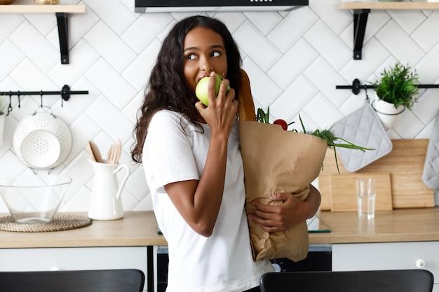 Piękna oliwkowa kobieta trzyma pakiet pełen jedzenia i je jabłko w nowoczesnej białej kuchni