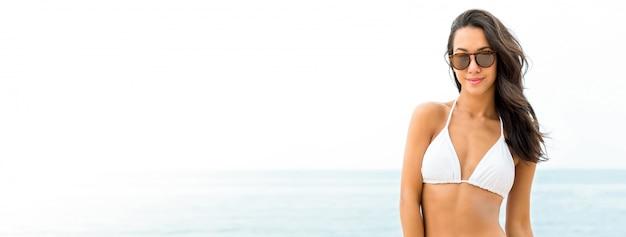 Piękna opalenizna azjatycka kobieta w swimsuit i okularach przeciwsłonecznych przy plażą