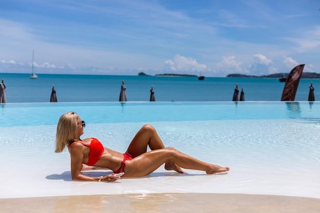 Piękna opalona, dopasowana kaukaski kobieta brązowa błyszcząca skóra w bikini z olejem kokosowym przy niebieskim basenie w słoneczny dzień