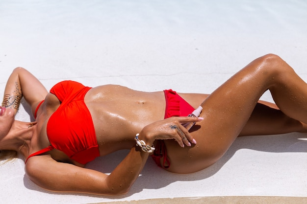 Piękna opalona, dopasowana kaukaski kobieta brązowa błyszcząca skóra w bikini z olejem kokosowym