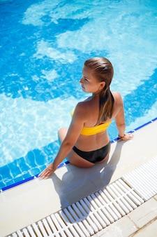 Piękna opalona dziewczyna w żółtym stroju kąpielowym w dużym basenie z niebieską wodą