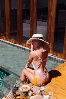 Piękna opalona kaukaski kobieta w bikini i słomkowym kapeluszu z pływającym śniadaniem w niesamowitej luksusowej willi w stylu bali w słoneczny dzień przy basenie, tropikalne tło.