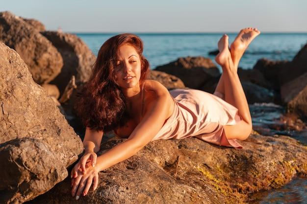 Piękna opalona kobieta w bieliźnie leży na przybrzeżnych skałach.