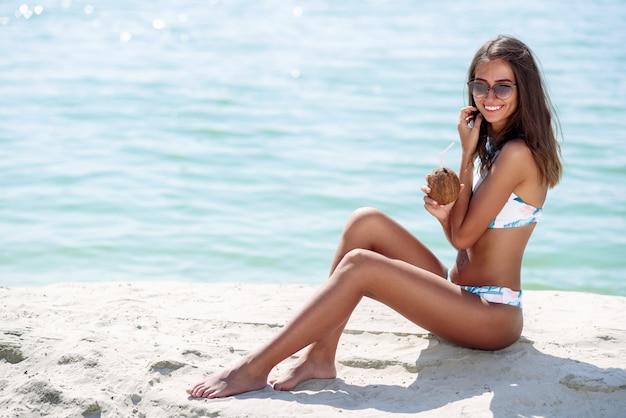 Piękna opalona kobieta w stylowych okularach przeciwsłonecznych i modnym bikini, relaksująca z kokosem na rajskiej plaży