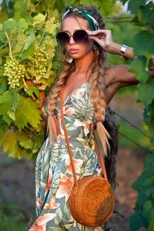 Piękna opalona kobieta w zielonej sukni z plecionymi włosami w okularach przeciwsłonecznych pozuje w winnicach we francji. uroda i moda.