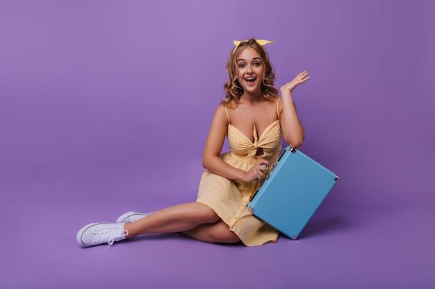Piękna opalona kobieta z zaskoczonym uśmiechem, zabawny pozuje z walizką. portret miłej dziewczyny niesamowite w jasnej sukience.