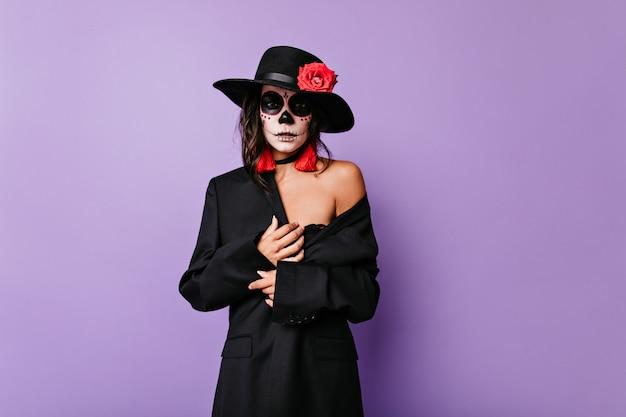 Piękna opalona kobieta ze sztuką twarzy, ubrana w czarną kurtkę i kapelusz, pozuje na liliowej ścianie.
