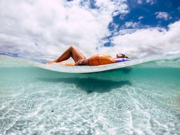 Piękna opalona młoda kobieta położyła się i zrelaksowała na modnym nadmuchiwanym lilo na rajskiej plaży z piaskiem i czystą, błękitną wodą - zdjęcie podwodne i na zewnątrz dla koncepcji wakacji i podróży