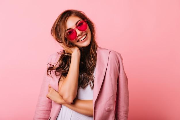 Piękna optymistyczna dziewczyna dotyka jej rude włosy. kryty portret błogiej białej modelki na różowym tle.