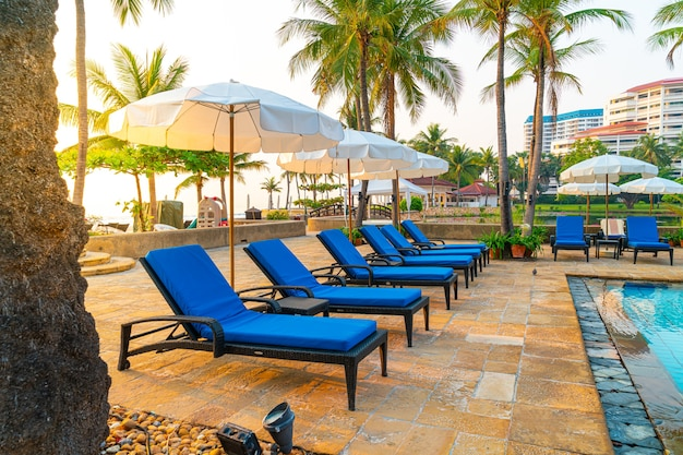 Piękna palma z basenem z parasolami w luksusowym hotelu o wschodzie słońca - koncepcja wakacji i wakacji