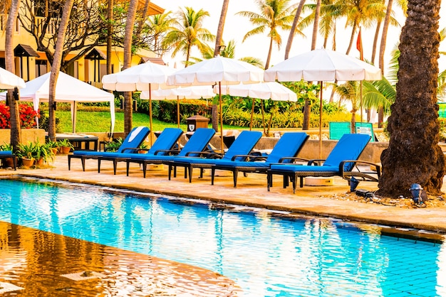 Piękna palma z parasolem w basenie w luksusowym hotelu o wschodzie słońca, koncepcja wakacji i wakacji