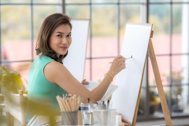 Piękna pani azji kobieta siedzi i za pomocą pędzla do bólu obraz w pokoju. pomysł na hobby, relaks lub pracę artystyczną w domu.