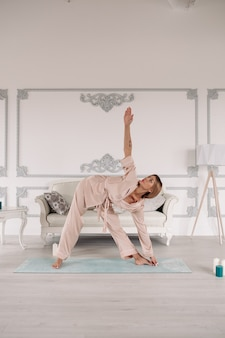 Piękna pani ćwiczy i siedzi w pozycji lotosu podczas odpoczynku w swoim mieszkaniu. koncepcja zdrowego i stylu życia