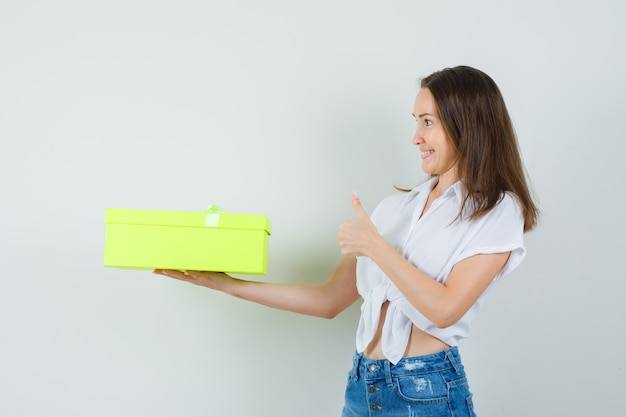 Piękna pani daje prezent komuś, pokazując kciuk w białej bluzce, widok z przodu dżinsy.