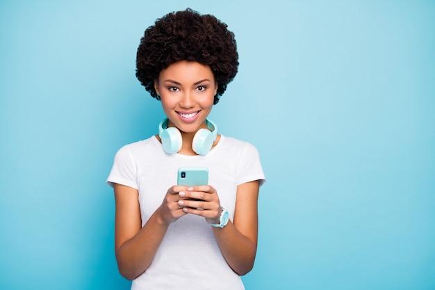 Piękna pani hipster trzymając telefon nosić słuchawki