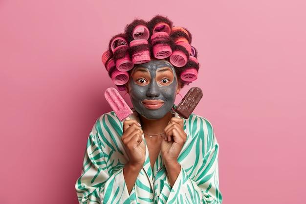 Piękna pani noszenie maski do pielęgnacji twarzy noszenie lokówek na białym tle