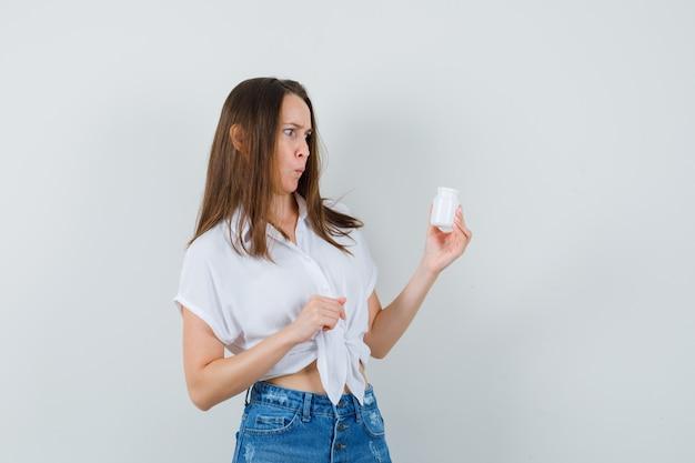 Piękna pani patrząc na butelkę tabletek w białej bluzce, dżinsach i wyglądająca na zdziwioną. przedni widok.