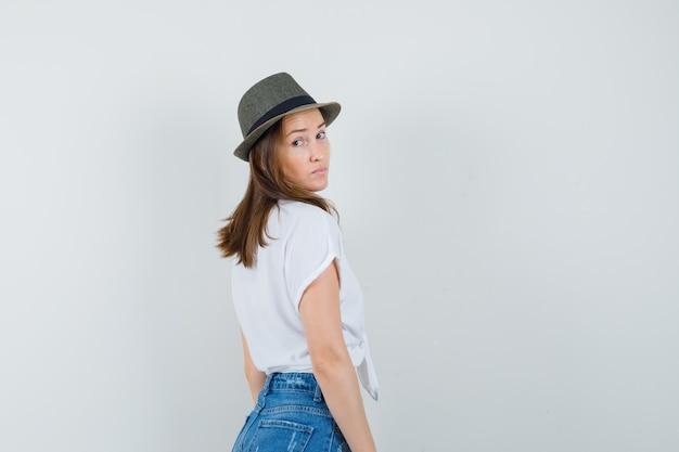 Piękna pani, patrząc wstecz w białej bluzce, widok z tyłu kapelusza. miejsce na tekst