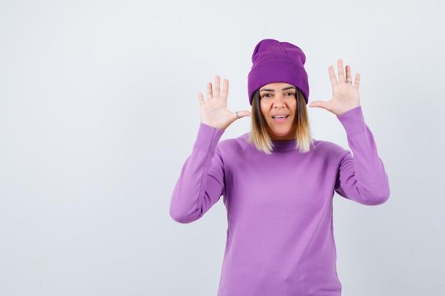 Piękna pani podnosząc ręce w geście kapitulacji w sweter, czapka i wesoły. przedni widok.
