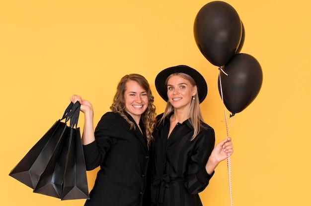 Piękna pani przyjaciele trzymając torby na zakupy i balony