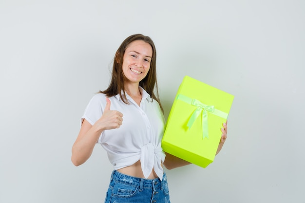 Piękna pani trzyma pudełko, pokazując kciuk w białej bluzce, dżinsach i wygląda pozytywnie. przedni widok.