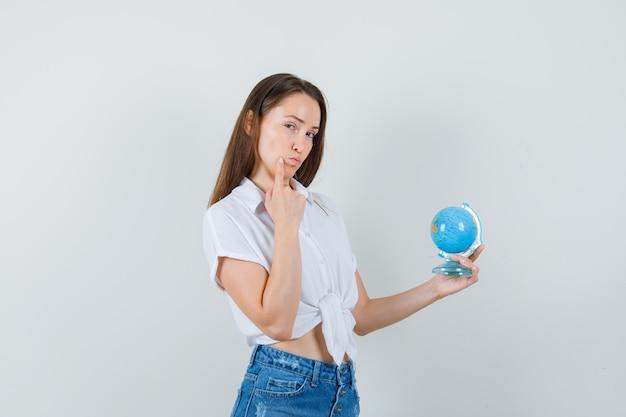 Piękna pani trzymająca kulę ziemską, myśląc coś w białej bluzce i patrząc zamyślony, widok z przodu.