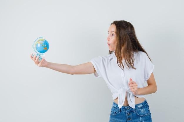 Piękna pani w białej bluzce daje komuś globus i patrzy na skupiony widok z przodu.