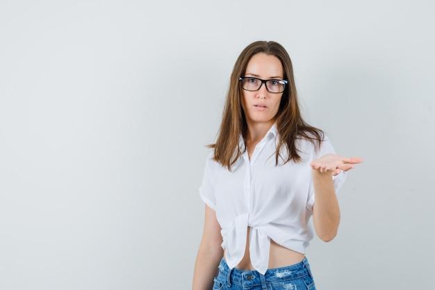 Piękna pani w białej bluzce, okulary podnoszące rękę z otwartą dłonią i wyglądająca na zadowoloną, widok z przodu.