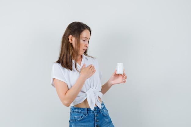 Piękna pani w białej bluzce patrząc na butelkę pigułek i patrząc skupiony, widok z przodu.