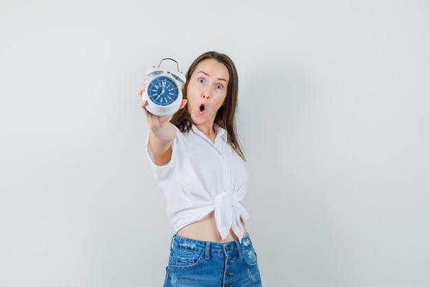Piękna pani w białej bluzce pokazuje zegar i wygląda zdziwiona, widok z przodu.