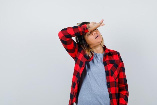Piękna pani w codziennych ubraniach cierpi na ból głowy i wygląda na zmęczoną, widok z przodu.