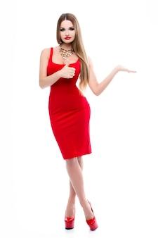 Piękna pani w czerwonej sukience z jaskrawym makijażem czerwone usta, wspaniały biust. młoda kobieta z długimi włosami, na szyi złoty naszyjnik. na białym tle długie nogi, czerwone buty na wysokich obcasach.
