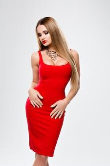 Piękna pani w czerwonej sukience z jaskrawym makijażem czerwone usta, wspaniały biust. młoda kobieta z długimi włosami, na szyi złoty naszyjnik. studio szare tło. uroda, moda, makijaż, katalog odzieży.