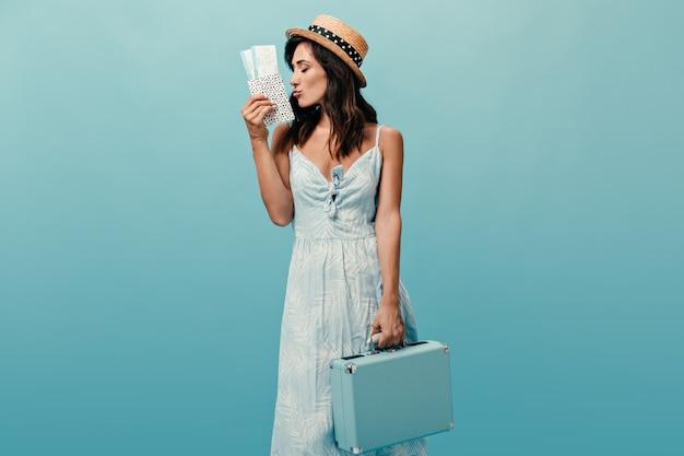 Piękna pani w słomkowym kapeluszu trzyma nowoczesną torbę i bilety na niebieskim tle. cudowna kobieta w letniej sukience pozowanie.