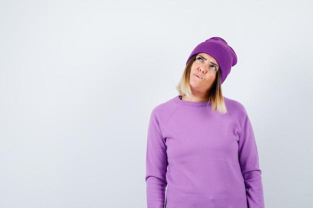 Piękna pani w swetrze, czapka patrząca w górę i wyglądająca na zaabsorbowaną, widok z przodu.