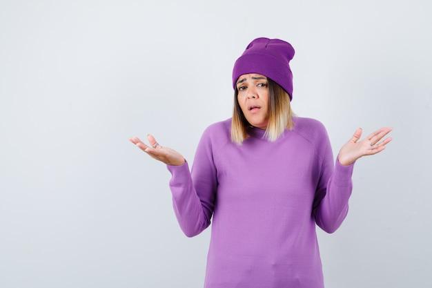 Piękna pani w swetrze, czapka pokazująca bezradny gest i wyglądająca na zaniepokojoną, widok z przodu.