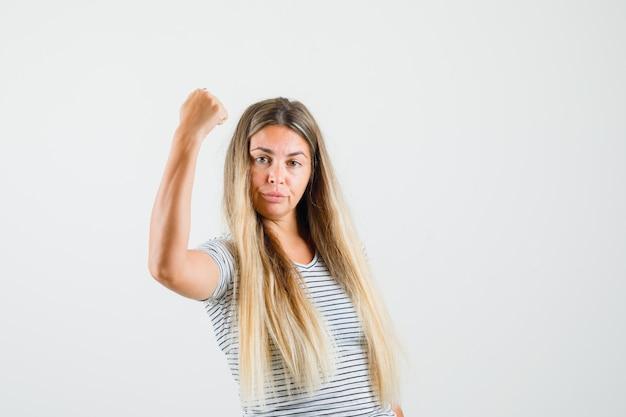 Piękna pani w t-shircie pokazująca siłę ramienia i wyglądająca potężnie, widok z przodu.