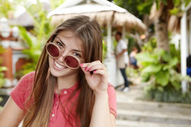 Piękna pani z długimi luźnymi włosami, zdejmująca okrągłe okulary przeciwsłoneczne z radosnym uśmiechem, miło spędzając czas na świeżym powietrzu podczas wakacji.