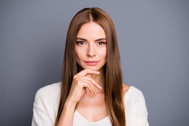 Piękna pani z długimi włosami, pozowanie na szarej ścianie